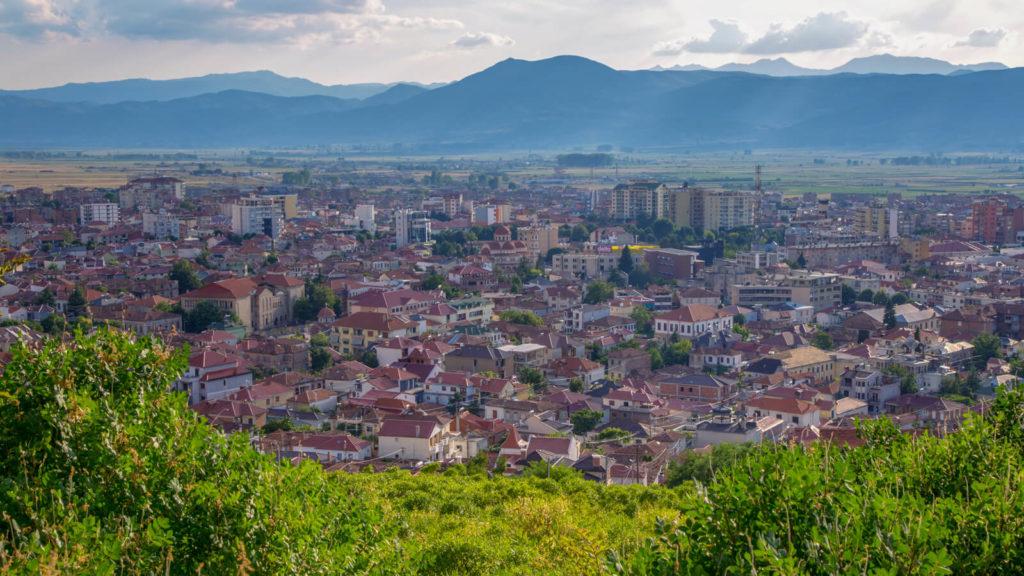 Blick über Korca in die Ferne mit Bergen und Feldern