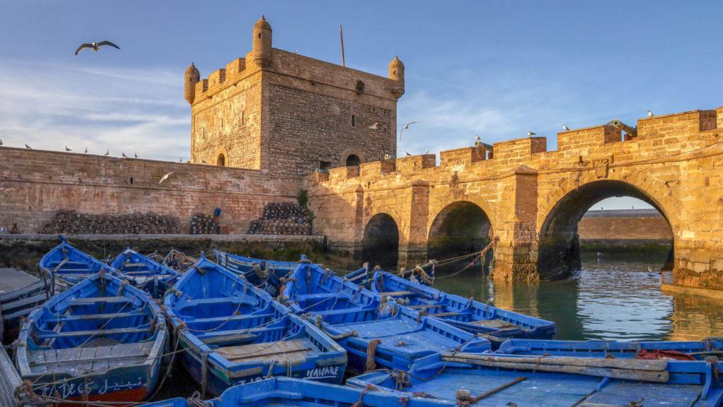 Fischerboote im Hafen von Essaouira und Blick auf die Festungsmauer