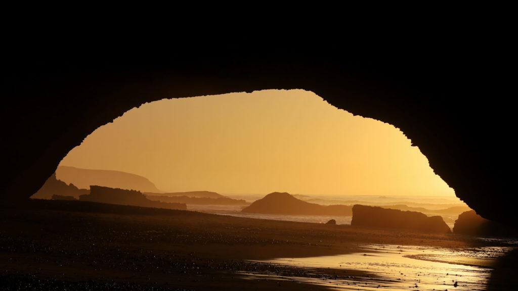 Blich aus dem Felsentor auf den Sonnenuntergang und das Meer am Legzira Beach