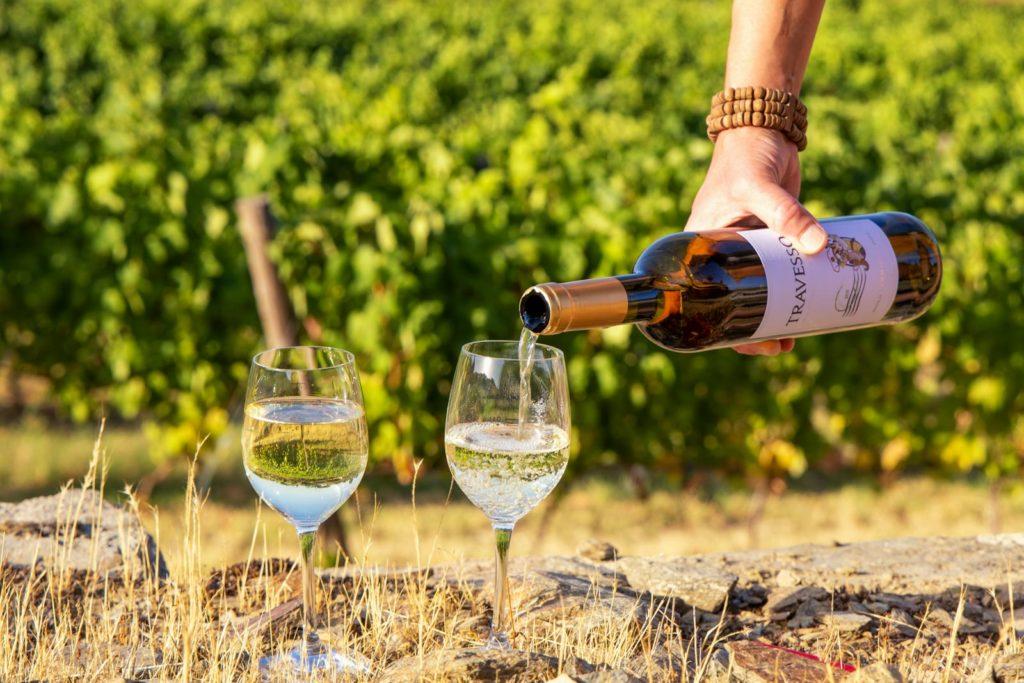 Zwei Weingläser und eine Flasche Weißwein in den Weinbergen im Douro-Tal
