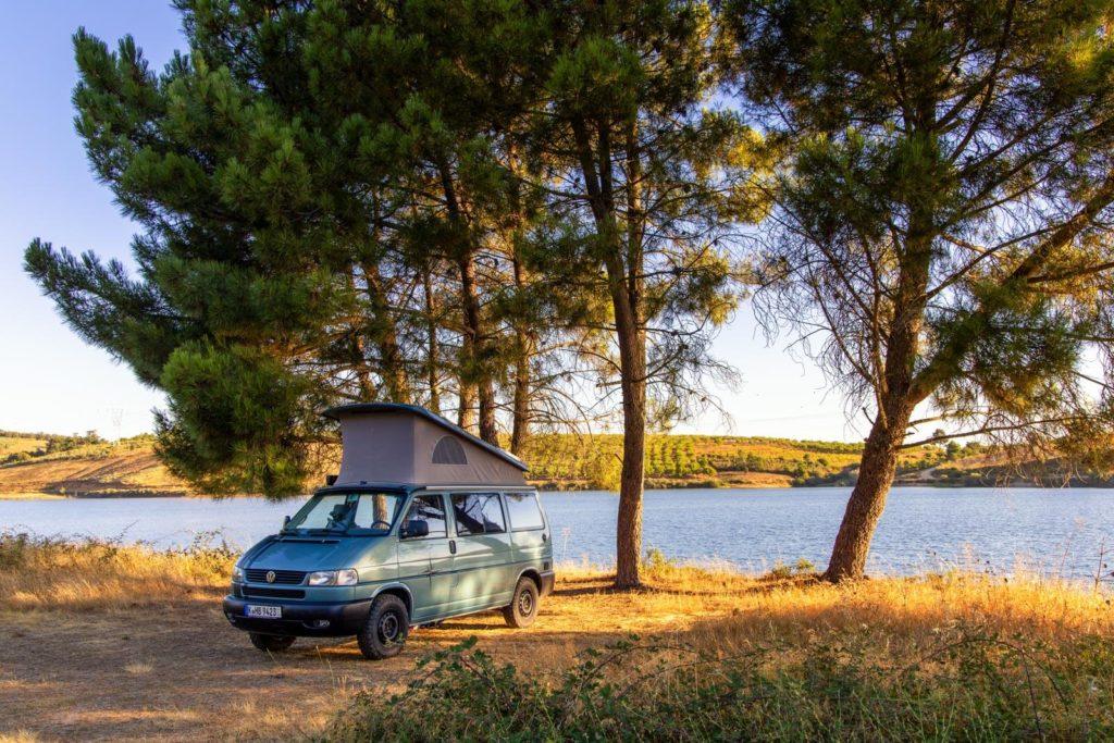 Camper auf freiem Wohnmobilstellplatz umgeben von Natur und einem kleinen See im Douro-Tal Portugal