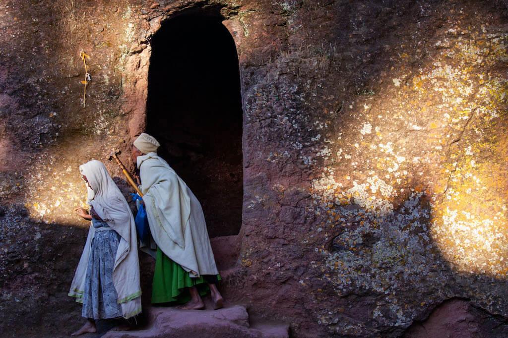 Gläubige Pilger küsst die Felswand beim Morgengebet in Felsenkirche in Lalibela - Äthiopien Reisebericht in Bildern